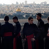 Priesthood seminary children participate in the traditional Palm Sunday procession on the Mount of Olives overlooking Jerusalem's old city, Sunday, March 28, 2010. Christians from around the world are commemorating Palm Sunday in Jerusalem, singing hymns and bearing palm fronds as they celebrate Jesus Christ's triumphant entry into the holy city 2,000 years ago. (AP Photo/Sebastian Scheiner)