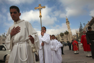 Catholic altar children participate in a procession before Palm Sunday mass at the Church of Nativity in the West Bank town of Bethlehem, Sunday, March 28, 2010. Palm Sunday commemorates Jesus Christ's triumphant entry into Jerusalem, and is the start of the Christian Holy Week. (AP Photo/Tara Todras-Whitehill)
