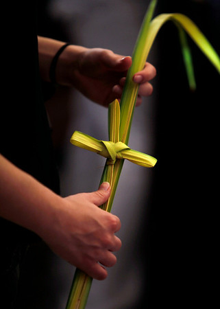 A person holds a palm frond bended into the shape of a cross during Palm Sunday mass at the Cathedral in Havana, Sunday, March 28, 2010. Palm Sunday commemorates Jesus Christ's triumphant entry into Jerusalem, and is the start of the Christian Holy Week.  (AP Photo/Javier Galeano)