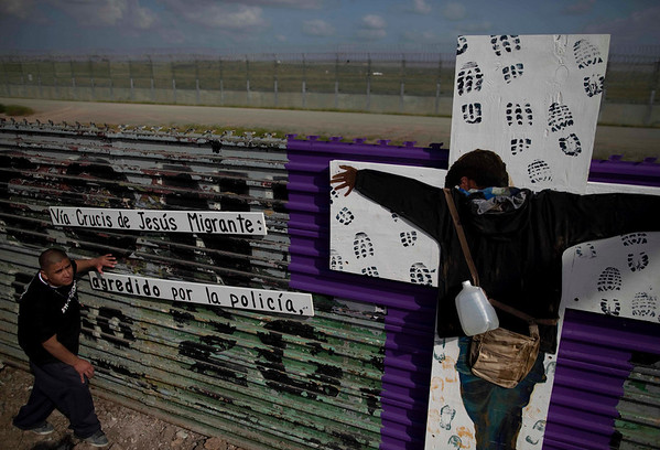 "A member of the Pro-migrant coalition hangs signs next to a cross at the US-Mexico border fence, symbolizing the ""Way of the cross of migrant Jesus"" due the holy week celebrations in Tijuana, Mexico, Friday, March 26, 2010. (AP Photo/Guillermo Arias)"