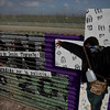"""A member of the Pro-migrant coalition hangs signs next to a cross at the US-Mexico border fence, symbolizing the """"Way of the cross of migrant Jesus"""" due the holy week celebrations in Tijuana, Mexico, Friday, March 26, 2010. (AP Photo/Guillermo Arias)"""