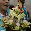 A woman offers palm fronds decorated with images of Jesus during Palm Sunday celebrations in Bogota. Sunday, March 28, 2010. Palm Sunday commemorates Jesus Christ's triumphant entry into Jerusalem, and is the start of the Christian Holy Week. (AP Photo/Christian Escobar Mora)