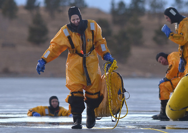 North Metro Fire Rescue District engineer Carisa Willibey carries a rescue board during ice rescue training at Siena Reservoir at Sheridan Parkway and Lowell Blvd. on Thursday. <br /> January 27, 2013<br /> staff photo/ David R. Jennings