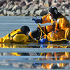North Metro Fire Rescue District firefighter Ed Feeley, right, prepares to attach a rope to  firefighter Craig Moilanen during ice rescue training at Siena Reservoir at Sheridan Parkway and Lowell Blvd. on Thursday. <br /> January 27, 2013<br /> staff photo/ David R. Jennings