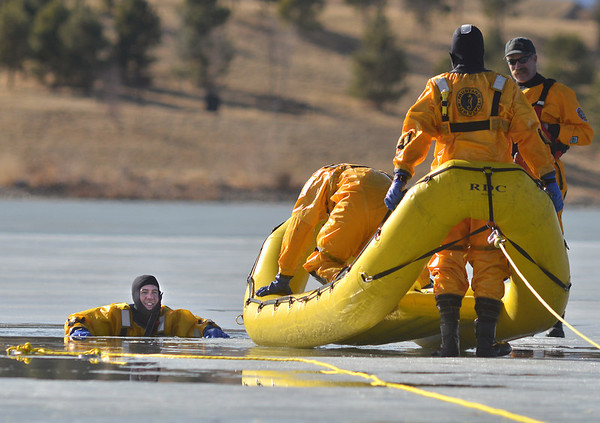 North Metro Fire Rescue District firefighter Craig Moilanen, left, waits to be rescued during ice rescue training at Siena Reservoir at Sheridan Parkway and Lowell Blvd. on Thursday. <br /> January 27, 2013<br /> staff photo/ David R. Jennings