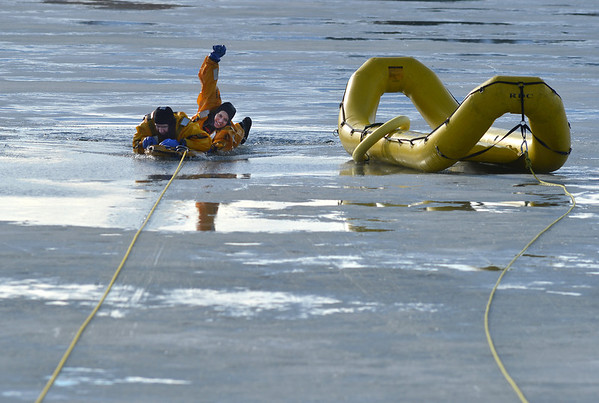 North Metro Fire Rescue District engineer Carisa Willibey, right, rescues firefighter Craig Moilanen during ice rescue training at Siena Reservoir at Sheridan Parkway and Lowell Blvd. on Thursday. <br /> January 27, 2013<br /> staff photo/ David R. Jennings