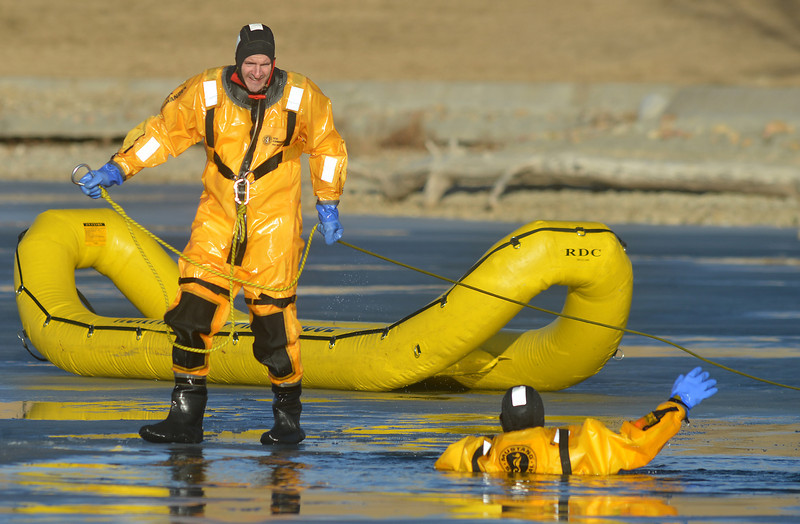 North Metro Fire Rescue District firefighter Doug Finley, left, prepares to rescue firefighter Craig Moilanen during ice rescue training at Siena Reservoir at Sheridan Parkway and Lowell Blvd. on Thursday. <br /> January 27, 2013<br /> staff photo/ David R. Jennings