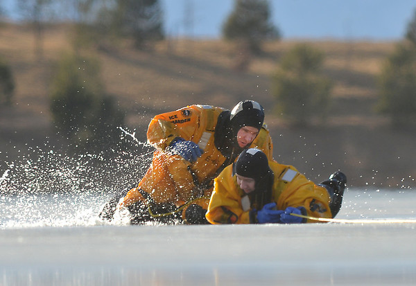 North Metro Fire Rescue District firefighter Dave Altizer rescues firefighter Craig Moilanen during ice rescue training at Siena Reservoir at Sheridan Parkway and Lowell Blvd. on Thursday. <br /> January 27, 2013<br /> staff photo/ David R. Jennings