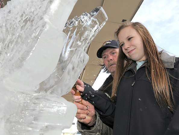 Chef Joel Hanson, helps Haley Strick, 17, right, with the proper techniques in sculpting in ice during Broomfield High School's Pro Start ice sculpting class at Garden Grill Catering on Wednesday.<br /> February 29, 2012 <br /> staff photo/ David R. Jennings