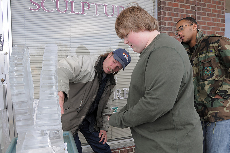 Chef Joel Hanson, left, gives ice scupting pointers to Morgan Browning, 17, and Theo Robison, 16,  during Broomfield High School's Pro Start ice sculpting class at Garden Grill Catering on Wednesday.<br /> February 29, 2012 <br /> staff photo/ David R. Jennings