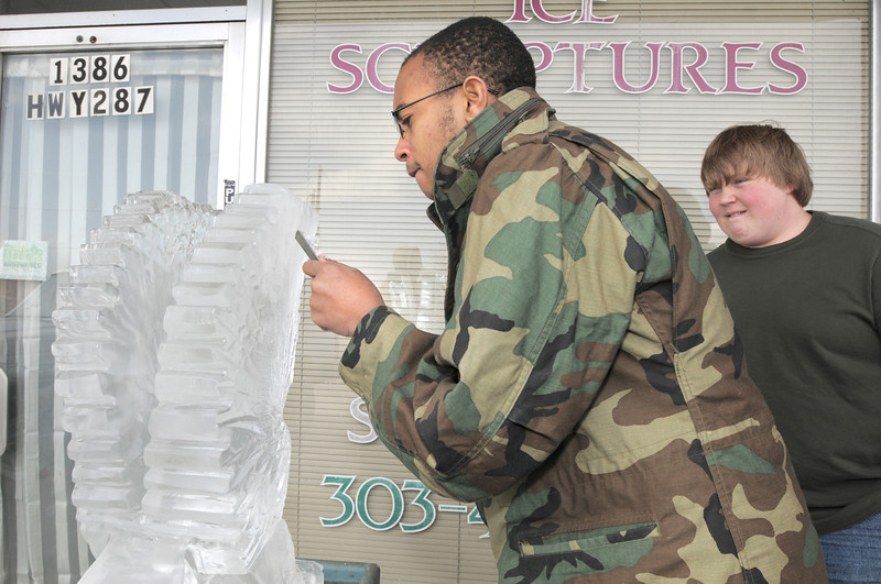 Theo Robison, 16, left, works on an eagle ice sculpture as classmate Morgan Browning, 17, right, watches during Broomfield High School's Pro Start ice sculpting class at Garden Grill Catering on Wednesday.<br /> February 29, 2012 <br /> staff photo/ David R. Jennings
