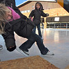 Hadley Olsen, 5, center, watches as her sister Samantha, 3, tries to get on the ice with help from their mother Marce as they skate at the Winter Skate ice rink in the Village at FlatIron Crossing mall on Saturday. <br /> <br /> December 12, 2009<br /> Staff photo/David R. Jennings