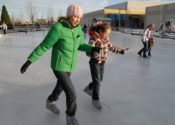 Kerri Dunn, left, helps her daughter Katlyn, 11, from Las Vegas, skate together at the Winter Skate ice rink in the Village at FlatIron Crossing mall on Saturday. <br /> <br /> December 12, 2009<br /> Staff photo/David R. Jennings