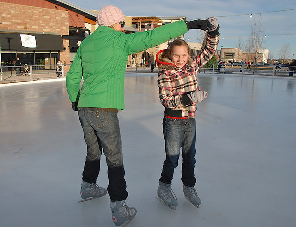 Kerri Dunn, left, helps her daughter Katlyn, 11,  spin while skating at the Winter Skate ice rink in the Village at FlatIron Crossing mall on Saturday. <br /> <br /> December 12, 2009<br /> Staff photo/David R. Jennings