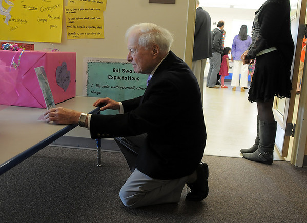 Harold Falzone, kneels to look at a photo of his late wife  Marlene Politzer, during the Bal Swan Children's Center open house celebration of the life of Marlene Politzer the director emeritus on Saturday.<br /> April 9, 2011<br /> staff photo/David R. Jennings