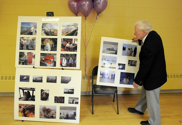 Harold Falzone, husband of Marlene Politzer , arranges a collection of photos from their trip to Antartica before the Bal Swan Children's Center open house celebration of the life of Marlene Politzer the director emeritus on Saturday. Politzer died on April 5th.<br /> April 9, 2011<br /> staff photo/David R. Jennings