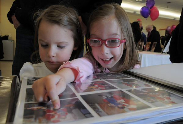 Riley Tuttle, 6, right,a former student,  shows her sister Cailen, 2, a current student, pictures of Santa in a scrap book during Bal Swan Children's Center open house in celebration of the life of Marlene Politzer the director emeritus on Saturday.<br /> April 9, 2011<br /> staff photo/David R. Jennings