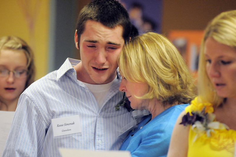 Reese Simonak and his mother Cathlynn Simonak, grandson and daughter of Marlene Politzer weep while Amazing Grace is sung during the Bal Swan Children's Center open house celebration of the life of Politzer on Saturday. Politzer died on Tuesday April 5th.<br /> April 9, 2011<br /> staff photo/David R. Jennings