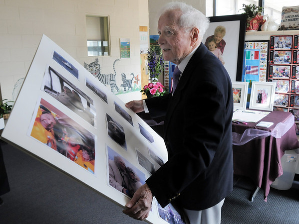 Harold Falzone, husband of Marlene Politzer , carries photos of their trip to Antartica for display at the Bal Swan Children's Center open house celebration of the life of Marlene Politzer the director emeritus on Saturday.<br /> April 9, 2011<br /> staff photo/David R. Jennings