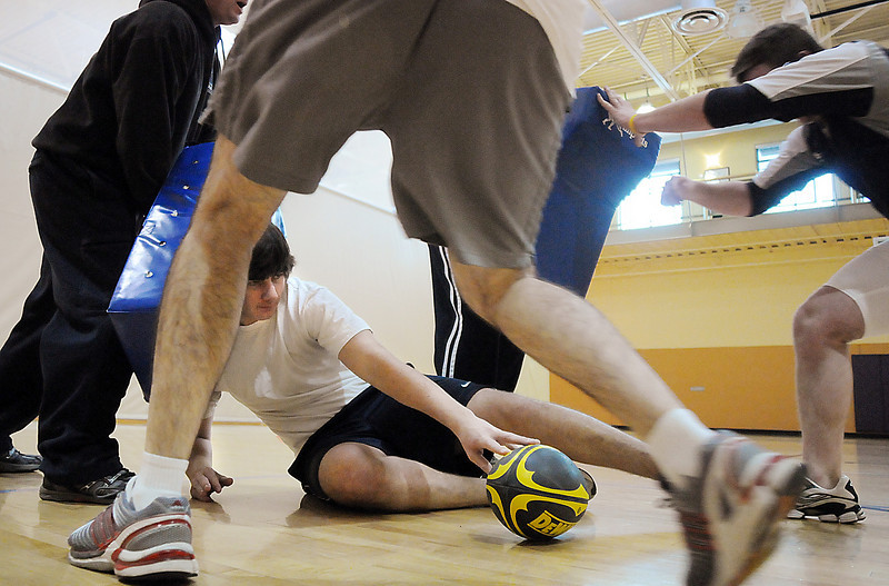 Daniel Sargeant, 17, on the floor, waits for a teammate to pickup the ball during practice with the Tigers Rugby Football Club at the Paul Derda Recreation Center on Saturday. <br /> <br /> January 02, 2009<br /> Staff photo/David R. Jennings