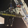 North Metro Fire Rescue paramedic Matt Gintzler rides with an injured worker for a technical rescue off of the roof of the Diamond Shamrock Station at 10th and US 287 on Wednsday evening. The worker suffered a dislocated knee while working on the roof of the building.<br /> December 22, 2010<br /> staff photo/David R. Jennings