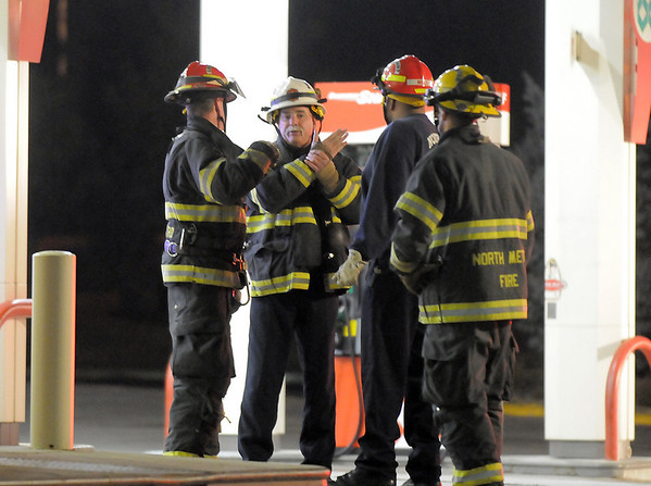 North Metro Fire Rescue District battalion chief, center, meets with firefighters and paramedics to plan the technical rescue of an injured worker on the roof of the Diamond Shamrock Station at 10th and US 287 on Wednsday evening. <br /> December 22, 2010<br /> staff photo/David R. Jennings