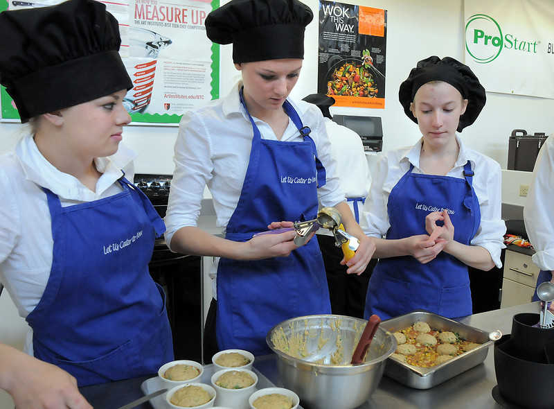 Broomfield High  Catering team members Sloan Tousignant, center, works on placing a corn bread topping on their casserole while Maddie Elliott, left, and Kelsey Ladtkow wait to help during the Iron Chefs competition by the  Boulder Valley School District-School Food Project at Broomfield High on Wednesday.<br /> May 4, 2011<br /> staff photo/David R. Jennings