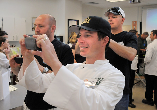 Chefs Brad DeFurio, Whole Foods, center, Hosea Rosenberg, Jax Fish House, and Bradford Heap, SALT Bistro, take pictures of the winning team the Broomfield High Catering during the Iron Chefs competition by the  Boulder Valley School District-School Food Project at Broomfield High on Wednesday.<br /> May 4, 2011<br /> staff photo/David R. Jennings