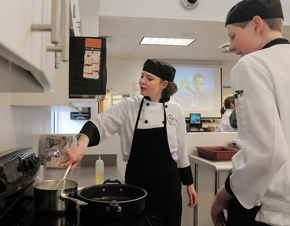 Abby Carlson, left, with the Broomfield HIgh ProStart team,  stirs the sauce with Adam Wolinski during the Iron Chefs competition by the  Boulder Valley School District-School Food Project at Broomfield High on Wednesday.<br /> May 4, 2011<br /> staff photo/David R. Jennings