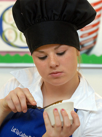 Maddie Elliott with Broomfield High Catering team smoothes out a corn bread topping for their casserole during the Iron Chefs competition by the  Boulder Valley School District-School Food Project at Broomfield High on Wednesday.<br /> May 4, 2011<br /> staff photo/David R. Jennings