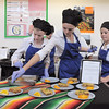 Broomfield High's Catering team of Kelsey Ladtkow, left, Sloan Tousignant and Maddie Elliott put final touches on their dishes for presentation to the judges during the Iron Chefs competition by the  Boulder Valley School District-School Food Project at Broomfield High on Wednesday.<br /> May 4, 2011<br /> staff photo/David R. Jennings