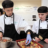 Broomfield High ProStart team members Isaac Wilson, left, adds ingredients to the casserole while Abby Carlson waits to smooth out the layer during the Iron Chefs competition by the  Boulder Valley School District-School Food Project at Broomfield High on Wednesday.<br /> May 4, 2011<br /> staff photo/David R. Jennings