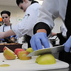 Issac Wilson, foreground cuts apples for the final presentation of the Broomfield ProStart team's casserole during the Iron Chefs competition by the  Boulder Valley School District-School Food Project at Broomfield High on Wednesday.<br /> May 4, 2011<br /> staff photo/David R. Jennings