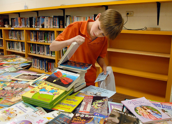 Michael Akers, 9, looks through free books after the Jump Start literacy and math camp student presentation at Emerald elementary School on Thursday.<br /> July 28, 2011<br /> staff photo/ David R. Jennings