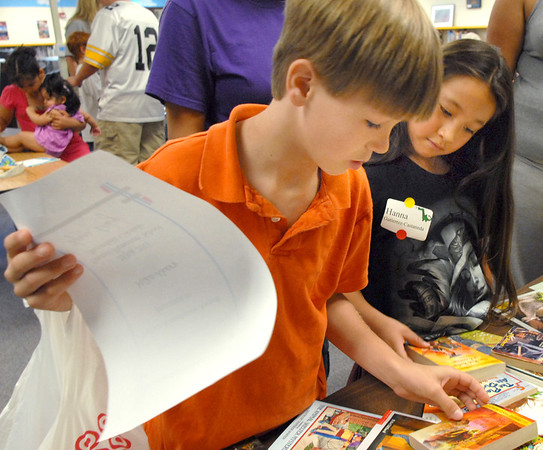 Michael Akers, 9, left, and Hanna Gutierrez-Castaneda, 8, look over free books after the student presentation of the Jump Start literacy and math camp at Emerald elementary School on Thursday.<br /> July 28, 2011<br /> staff photo/ David R. Jennings