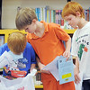 Chase Akers, 6, left, checks out his goodie bag with his brothers  Michael, 9, and Tony, 8, after the student presentation at the Jump Start literacy and math camp at Emerald Elementary School on Thursday.<br /> July 28, 2011<br /> staff photo/ David R. Jennings