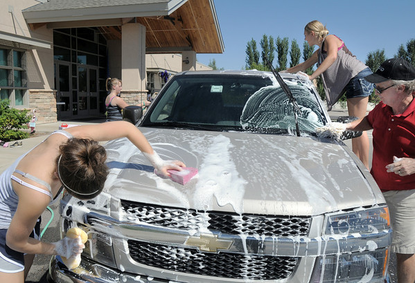 Audra Hedberg, 16, left, Christina Nuss-Brill, 17, and Tom Shannon wash a car during Saturday's Kelsey Marie Shannon memorial carwash at Family of Christ Church .<br /> August 27, 2011<br /> staff photo/ David R. Jennings
