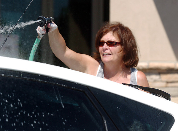 Dottie Shannon rinses a car during Saturday's Kelsey Marie Shannon memorial carwash at Family of Christ Church .<br /> <br /> August 26, 2011<br /> staff photo/ David R. Jennings