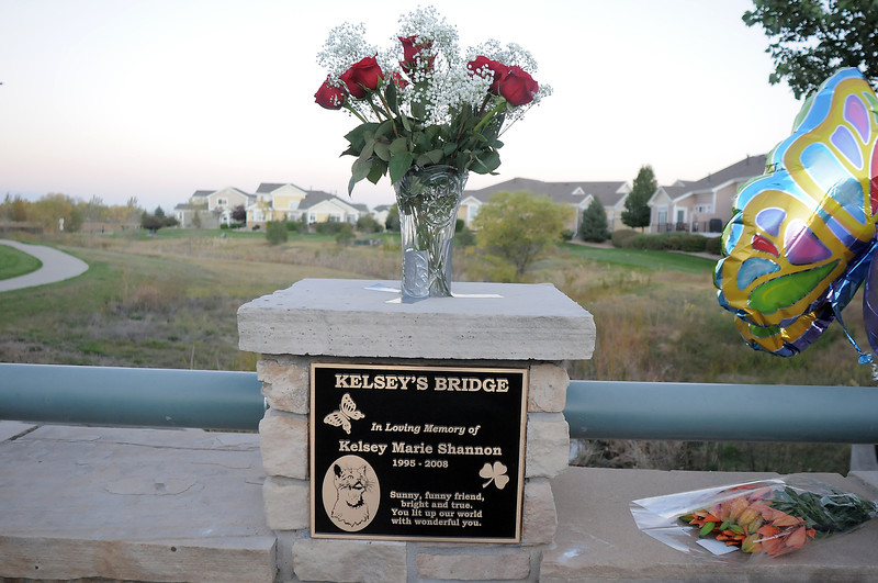 Flowers adorn the plaque after the dedication of Kelsey's Bridge in memory of Kelsey Marie Shannon on Lowell Blvd. in the Broadlands on Friday.<br /> October 14, 2011<br /> staff photo/ David R. Jennings