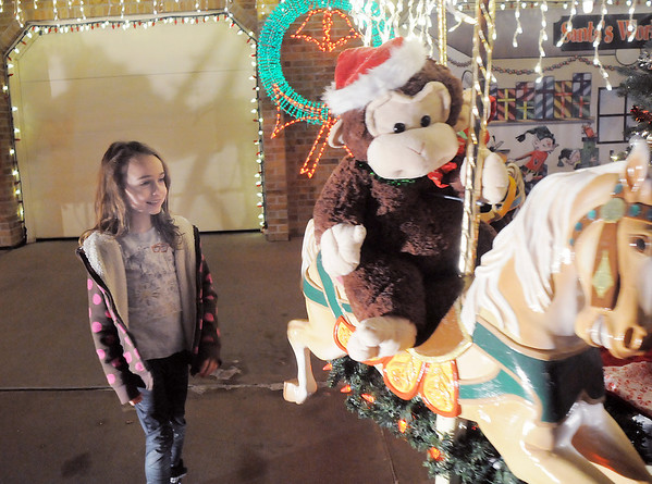 """Jostyn Hillesheim, 6, looks at the carousel in Kim Weibert's holiday lighting display at 1188 Clubhouse Drive.<br /> More photos please see  <a href=""""http://www.broomfieldenterprise.com"""">http://www.broomfieldenterprise.com</a><br /> December 9, 2011<br /> Staff photo/ David R. Jennings"""
