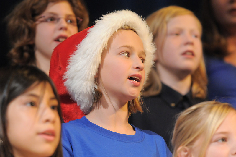 Fourth graders Ellie Gentry, center, wearing her Santa hat, sings with Naomi Agustin, left, and Jonah French-Jurgens during the performance of the Kohl Elementary Holiday Choir for seniors at the Audi on Friday.<br /> <br /> December 8, 2011<br /> Staff photo/ David R. Jennings