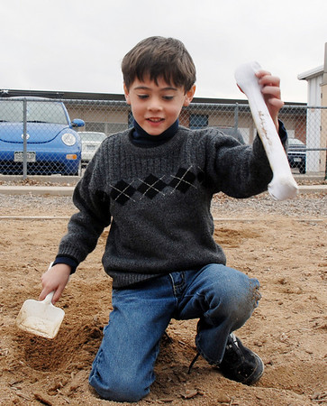 Jeremy Mena lifts a plastic dinosaur bone from the playground during Kohl Elementary School's Friday afternoon K-CARE program.<br /> November 13, 2009<br /> Staff photo/David R. Jennings