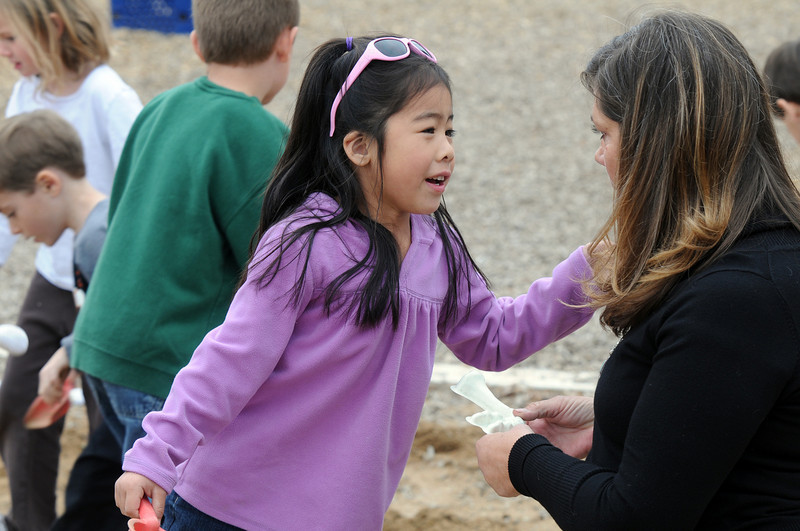 Allison Tanigawa talks to her teacher Leigh Ann Pollock after discovering a plastic dinosaur bone in the playground during Kohl Elementary School's Friday afternoon K-CARE program.<br /> November 13, 2009<br /> Staff photo/David R. Jennings