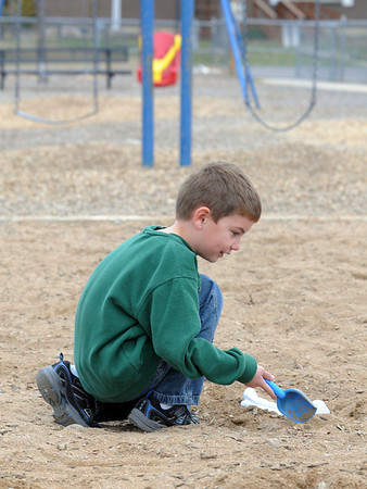 Kindergartner Joshua Broussard digs up a plastic dinosaur bone in the playground during Kohl Elementary School's Friday afternoon K-CARE program.<br /> November 13, 2009<br /> Staff photo/David R. Jennings