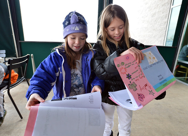 Kohl Elementary fourth graders Lauren Weiss, left, and Ashlin Blackford read a poem together during Mrs. Fields' Poetry Cafe class at the 287 and Miramonte Starbucks on Friday.<br /> <br /> December 14, 2012<br /> staff photo/ David R. Jennings
