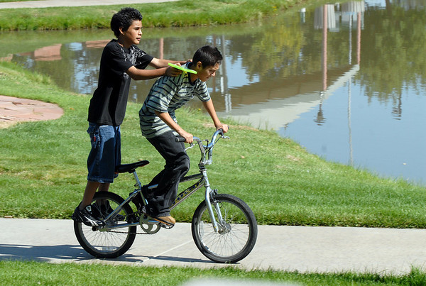 Boys ride past the Community Park Pond on their way to deliver a DVD to the library during Labor Day weekend on Saturday.<br /> <br /> Sept. 5, 2009<br /> Staff photo/David R. Jennings