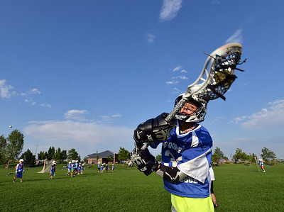 Jake Borelli, 11, catches the ball  during Monarch High School's David Auday lacrosse camp at the Broomfield County CommonsPark on Thursday.   July 12, 2012 staff photo/ David R. Jennings  More photos and video please go to  www.broomfieldenterprise.com
