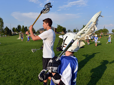 Assistant coach Philip Bubernak, 15, left, demonstrates  how to throws left to Ethan Wagner, 11,  during Monarch High School's David Auday lacrosse camp at the Broomfield County CommonsPark on Thursday.  July 12, 2012 staff photo/ David R. Jennings  More photos and video please go to  www.broomfieldenterprise.com