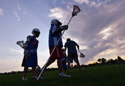Lacrosse players work on their skills as the sun sets during Monarch High School's David Auday lacrosse camp at the Broomfield County CommonsPark on Thursday.  July 12, 2012 staff photo/ David R. Jennings  More photos and video please go to  www.broomfieldenterprise.com