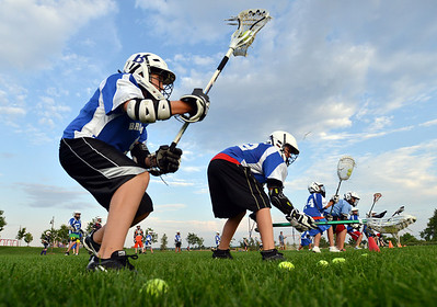 Zach Cammer, 13, left, and Zach Young, 10, run to the line to scoop up a ball for a game during Monarch High School's David Auday lacrosse camp at the Broomfield County CommonsPark on Thursday.  July 12, 2012 staff photo/ David R. Jennings  More photos and video please go to  www.broomfieldenterprise.com